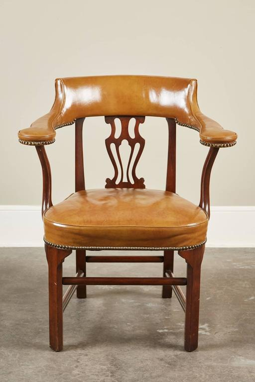 A unique pair of Mid-Century Modern American mahogany and leather armchairs with an abstract urn-like shaped splat. The crest rail is upholstered with the leather that continues onto the armrests and is held together by nailheads.