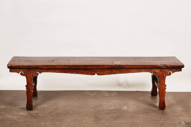 An 18th century Chinese low sword leg bench or table with intricate carvings all along the legs.
