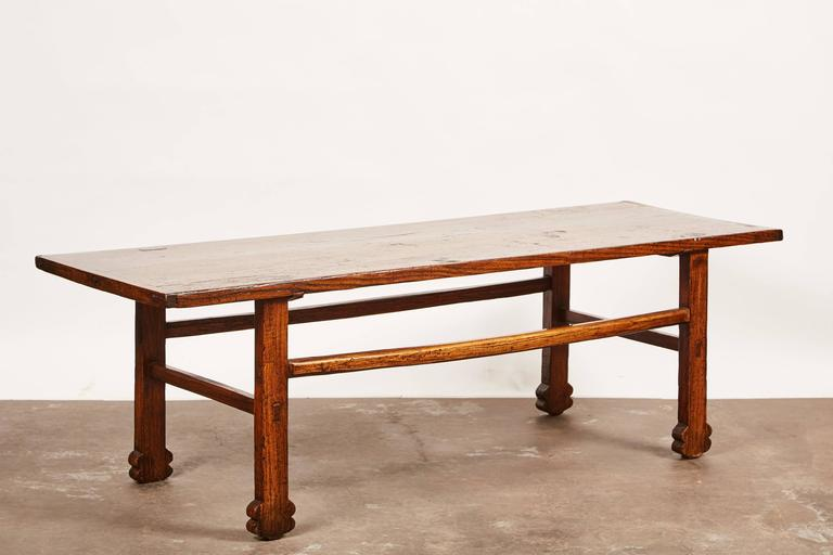 "A ""one of a kind"" kang table - otherwise known as either a low table or a chair-level bed- with solid elmwood tabletop and plum feet. The table is originally from Shanxi, China."