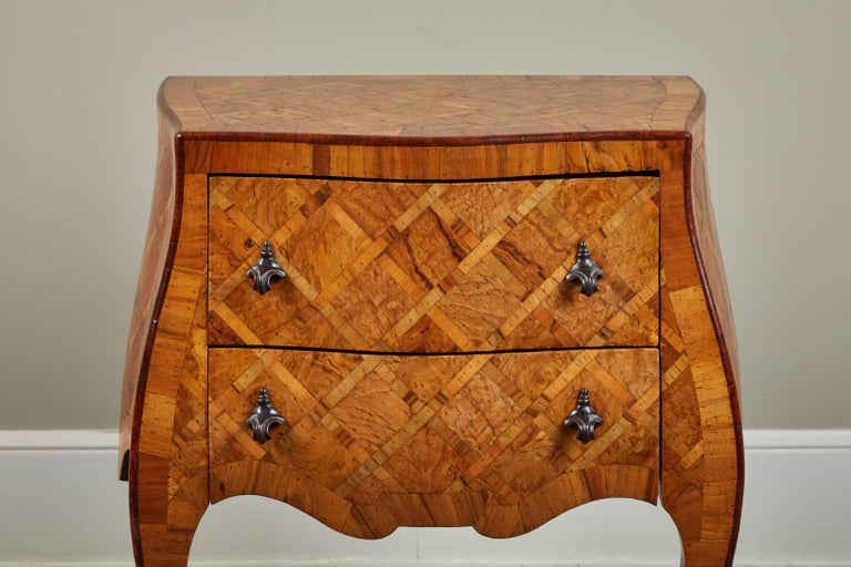 An early 20th century petite Italian marquetry chest of drawers. Gorgeous dark hardware on two drawers.