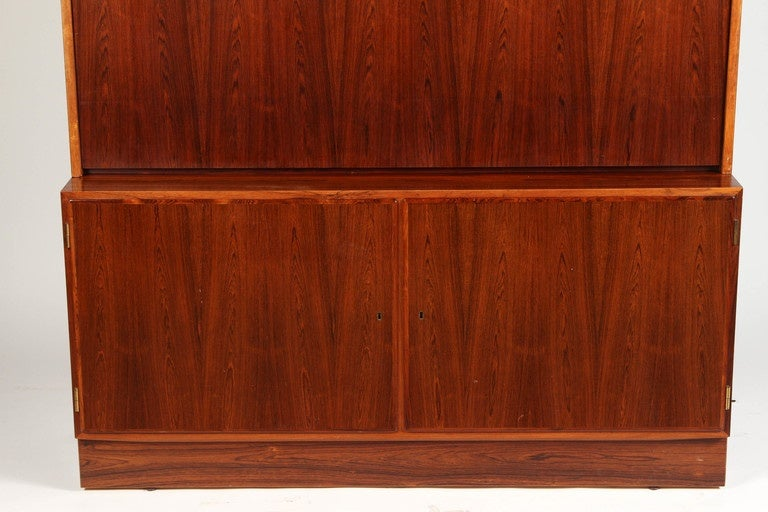 A 1970s Danish palisander rosewood desk with adjustable shelves on the inside, both below and above the working surface of the desk. The center cabinet door folds down to be the writing surface.