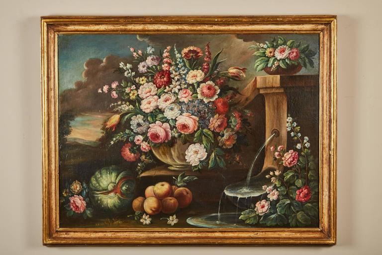 A 19th century Italian school life large oil-on-canvas painting within a gilt wood frame painting depicts a vase with a floral arrangement, a fountain and fruit, within a landscape in the background, a light fixture attached to the frame.