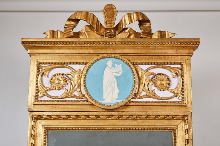The console with a veined white marble top, the frieze carved with foliate design motifs and central medallion on tapered fluted legs. The rectangular mirror plate within robed border surmounted by a rectangular top crest with a medallion within