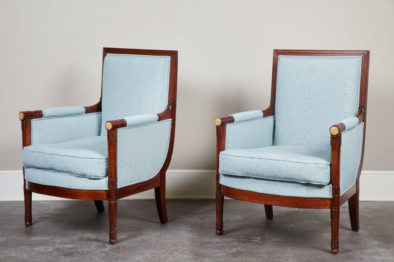 A handsome pair of French Empire mahogany bergeres, circa 1810. Turned legs with foliage carving details and brass trim details.