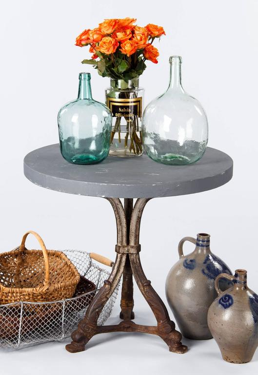 A French Art Nouveau gueridon table from Provence, circa 1910s. The tripod forged iron base features acanthus leaves and scroll designs. The round thick concrete top has been painted in metallic grey. A great table that can be used inside or