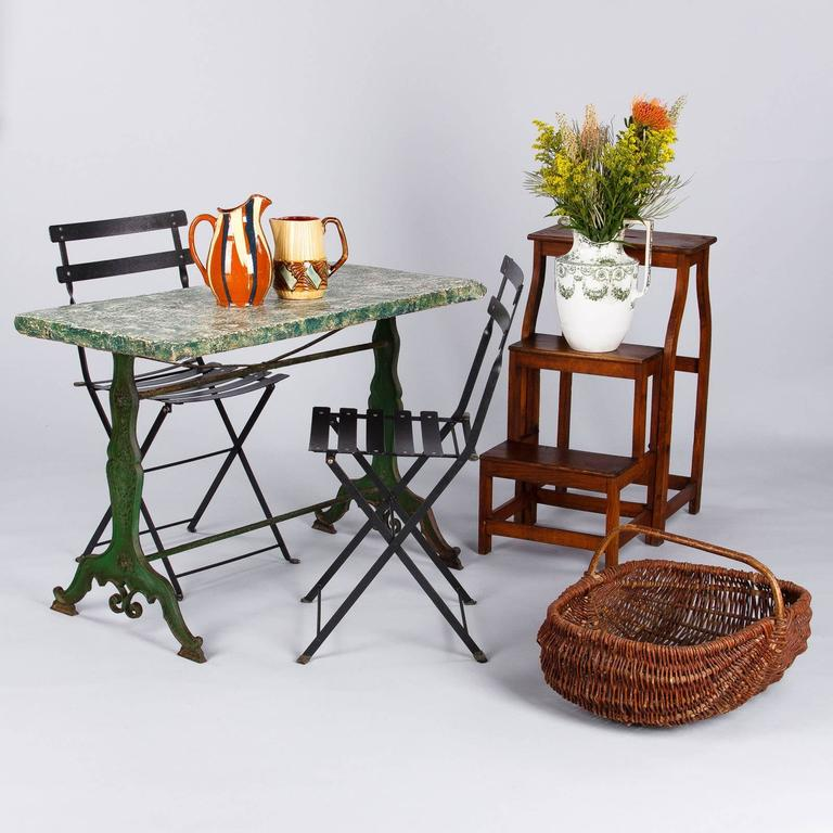 A French green garden table from Provence, late 1800s, featuring a wonderful cast iron base with a dark green aged patina and shaped legs with carved motifs and scrolls. The top is a slab of concrete that was later sponge painted in white and
