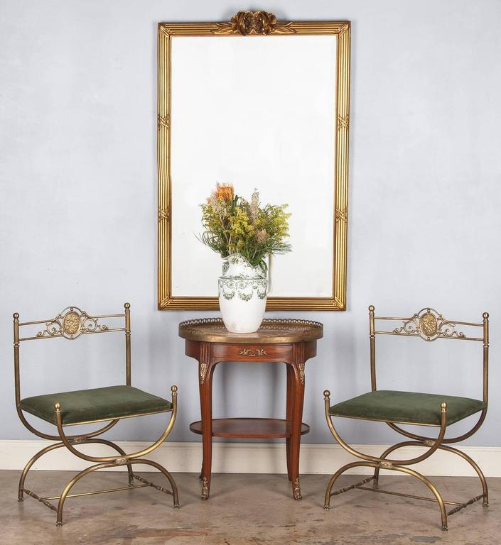 An elegant giltwood mirror in the Louis XVI style that was purchased in the Beaujolais Region. The frame has a fascia molding and cross ribbon motifs with carved roses at the crest. The mirrored glass is beveled.