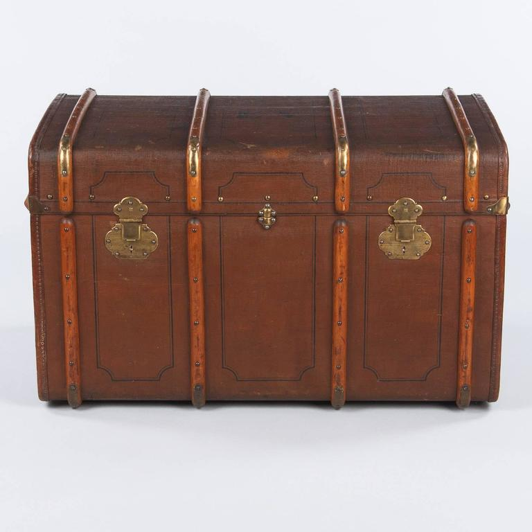 A French traveling trunk from the early 1900s purchased in Lyon. The trunk is made of poplar lined with a dark brown oil cloth with a black trim and the engraved initials E.V. The side handles are leather and the locks are brass. The inside features