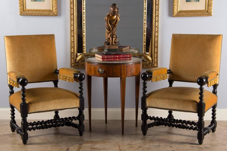 Stylish looking pair of Louis XIII style armchairs that date from the Napoleon Period, circa 1870s. The ebonized pear wood frame features baluster and spiral legs and stretcher. The armrests terminate with a ball. The upholstery is velvet in gold