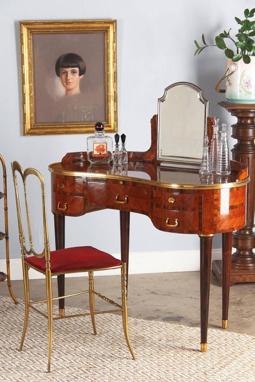 A rare, top quality, beautifully crafted kidney shaped vanity table in the Louis XVI Style by Gustave Keller. The dressing table, circa 1890s, is made of marquetry rosewood and violet wood and rests of cylindrical tapered legs finished with brass