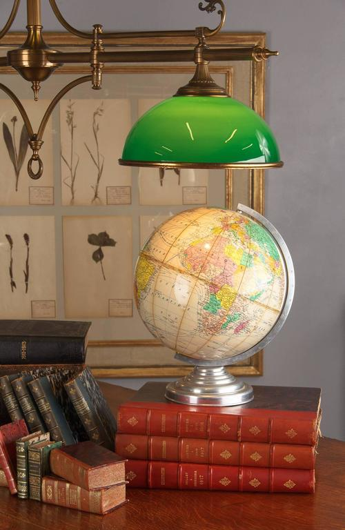 A 1960s terrestrial globe made in France with a papier mâché sphere rotating on an aluminium support.