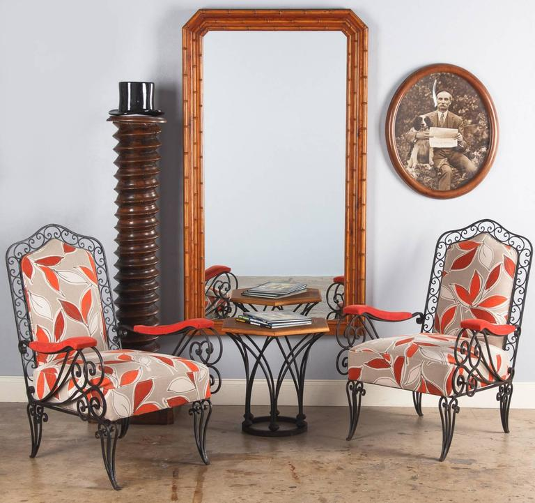A great pair of 1940s wrought iron armchairs that were recently re-upholstered with a colorful fabric featuring leaf motifs in light grey, orange and coral tones. The black iron frames are all scrolled. The seats are firm and comfortable. Perfect