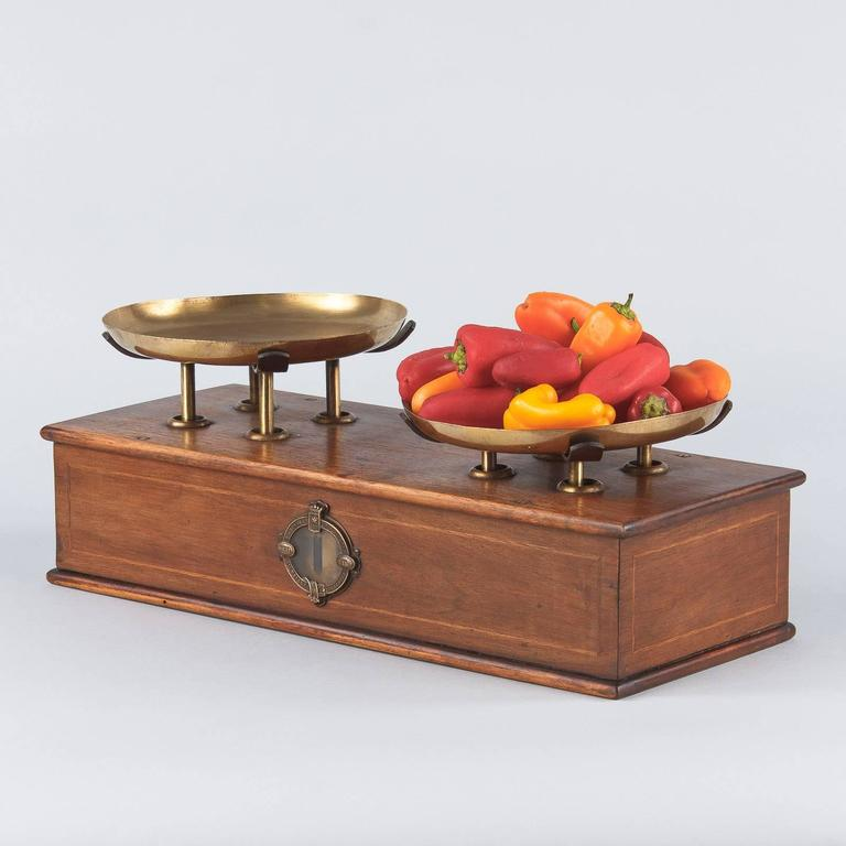 A French counter scale in warm walnut and brass, circa 1880s. The scale is made of walnut wood, each side has a simple thin inlaid square of lighter toned wood. Either side has a glass front dial with a decorative brass ring. The two plateaux are