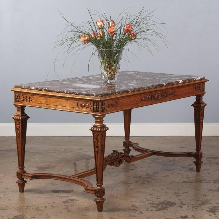 "An elegant, stately center table made of golden oak with a red Languedoc marble top in the Louis XIV style, circa 1860s. These tables were called ""Tables a Gibier"" (wild fowl and game) and were used by hunters to drop their prey. A very"