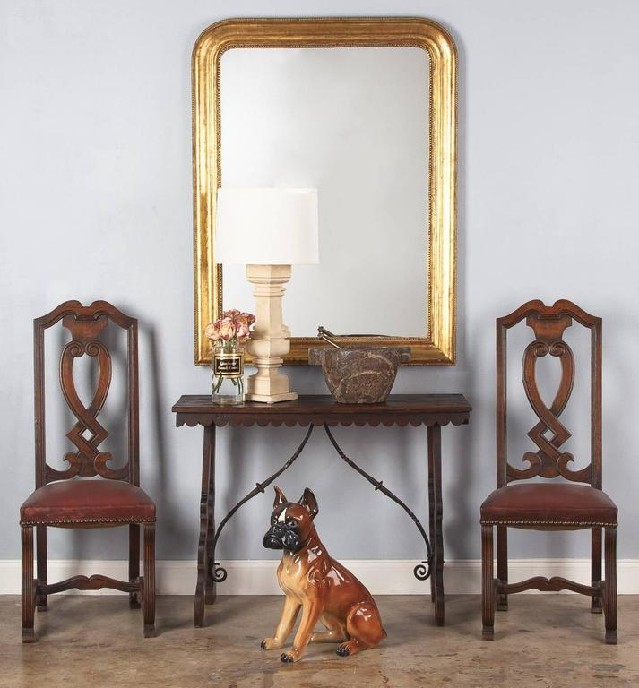 A late 1800s console table from Spain made of dark stained pinewood with a scrolled and twisted iron stretcher. The shaped legs are curved and the feet are rounded. The top is fixed with antique hand-forged nails and features a scalloped apron in