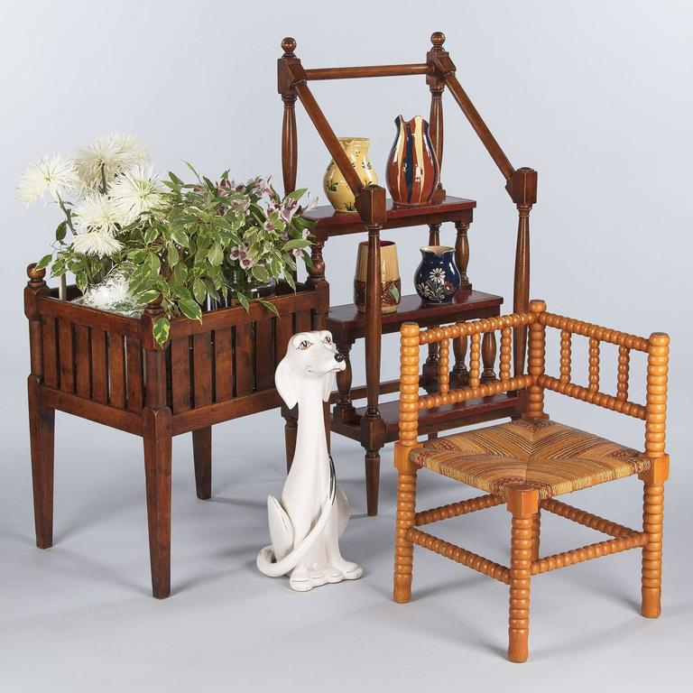A Country style French planter made of walnut wood. The antique jardiniere stands on four tapered legs, each has simple turning and shaping at the box corners and is topped with a knob finial. The sides and bottom of the box are comprised of walnut