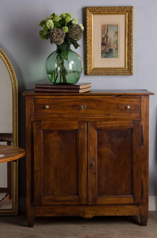A lovely Louis Philippe period two-door buffet made of walnut wood with a splendid age patina. The single drawer has brass pulls and key escutcheon in the shape of a shield. Beautiful antique hinges and a diamond escutcheon adorn the paneled doors.