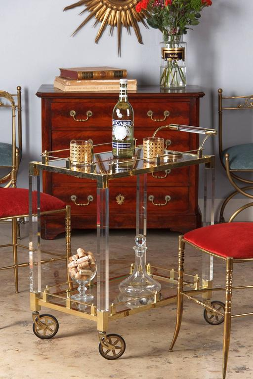 A wonderful bar cart from Spain, circa 1970s. The cart features brass rails and frames, lucite legs and a brass and lucite curved handle. Clear glass trays at top and bottom. It rolls on brass wheels with rubber tires.  Minor discoloration on brass.