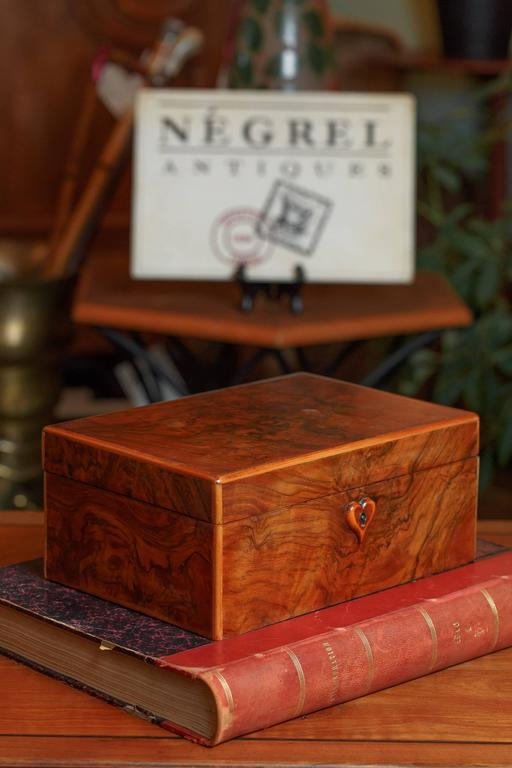 An antique jewelry box made of burl walnut veneer, circa 1900. Rich, warm burl walnut veneer with dreamy veining covers the top and all sides of the box. Lighter edge trim and the heart shaped key escutcheon are made of maple. The interior is