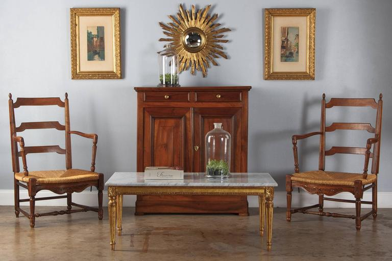 A pair of Louis XVI style beech wood and rush armchairs, circa 1940s. In typical Provençal style, the armrests are set back on the seat and the backs are fairly open, with simply shaped slats. Curved armrests sit on turned and fluted supports.