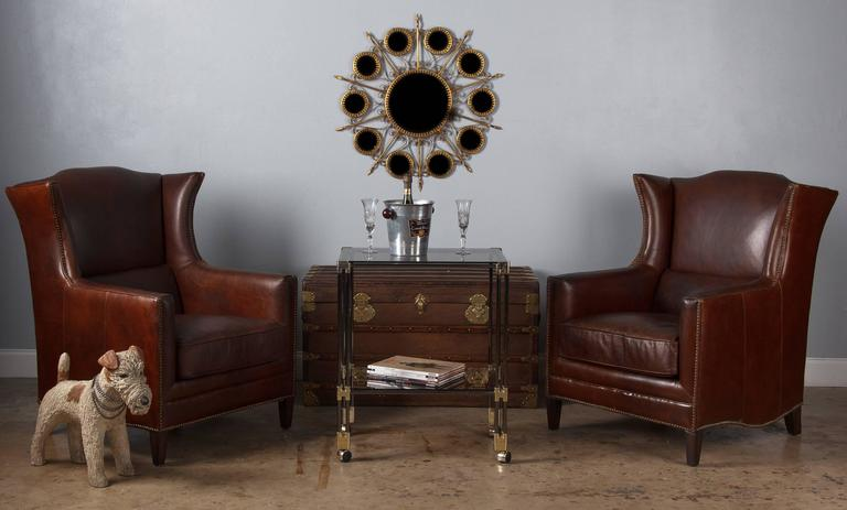 A pair of French wingback armchairs in rich brown leather, circa 1980. These armchairs have wonderful silhouettes, with a slight flare to the wingbacks, scalloped tops and curved edges along the lower sides. The leather is a deep, chocolate brown