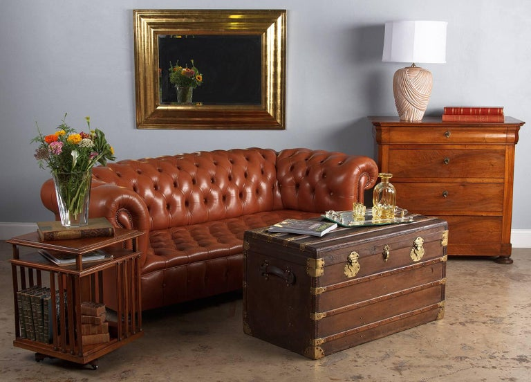A vintage Chesterfield three-seat sofa in caramel colored tufted leather, circa 1960s. Tight button tufts dot the seat, backrest, arms and front, the sides and back are flat. Antique nailhead trim highlights the front corners and graceful curve of