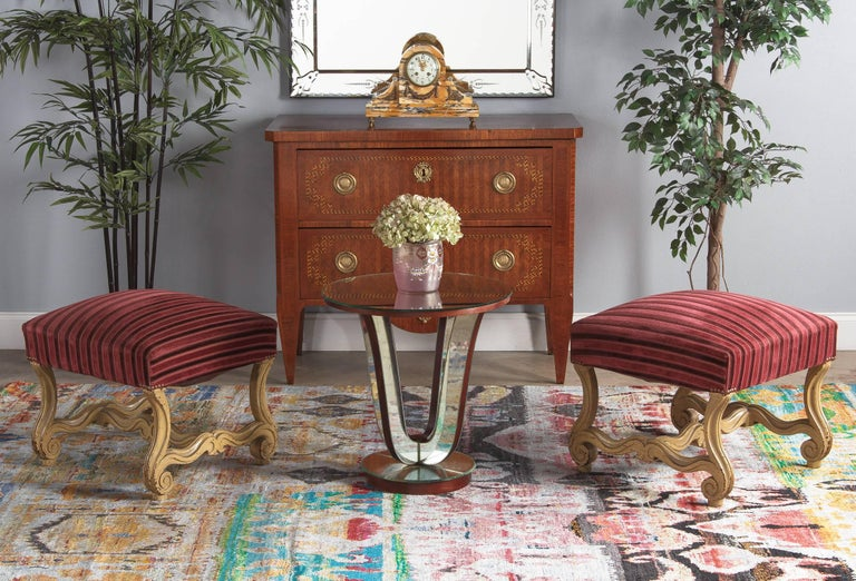 A lively pair of Louis XIV Style painted and upholstered ottomans or stools, circa 1900. Heavy beech wood bases feature curved and fluted legs with broadly scrolled feet, connected by undulating H-stretchers with matching motif. The bases are