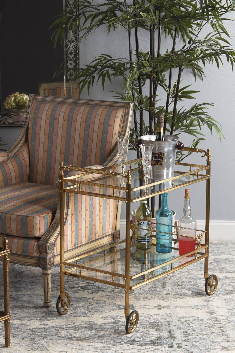 A fabulous midcentury brass and glass two-tiered bar cart attributed to Maison Baguès, circa 1950. Fluted brass frame, legs and handles. Each end has its own decorated handle, fluted at the center with textured and gracefully curled scrolls that