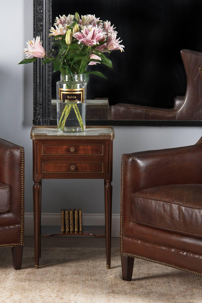 A Louis XVI style mahogany bedside cabinet nightstand with Carrara marble top, circa 1920. Chic and practical with two drawers and a bottom shelf, this piece will bring both style and utility to your space. Will also make a great end table. The