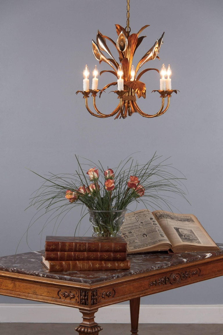 A very decorative gilded metal chandelier with an antique finish. The fixture has six arms newly rewired for candelabra bulbs. The chandelier is designed with leaves tightened with a rope and silver metal lilies with crystal prisms as pistils. The