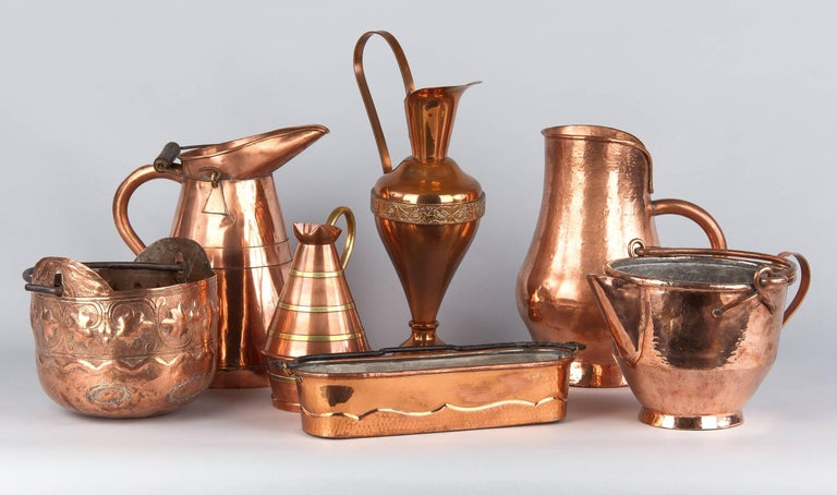 An attractive copper pitcher with embellishments, French, circa 1900. This wide pitcher features a large pour spout with built in strainer, a generous handle at the back as well as a swinging handle at the top with finely grooved texture. The top