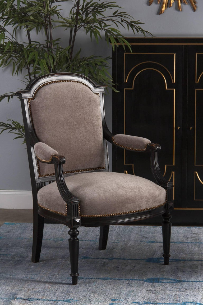 A Napoleon III Period armchair in ebonized pear wood. It has been recently re-upholstered in a fine neutral gray with a velvety feel, finished with antiques nails. The wide, comfortable armchair has an arched top, curved and fluted armrests with