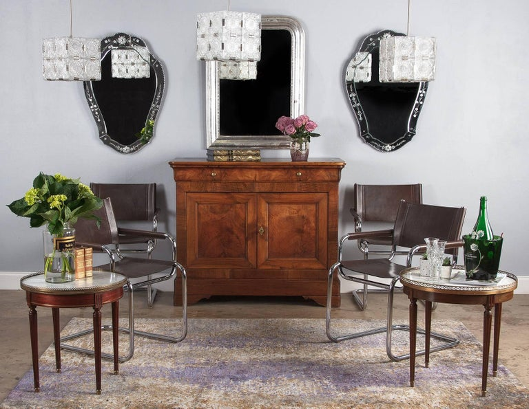 Three stylish cut-glass pendant lights, circa 1970. Cubed form with four sides and bottom comprised of cut-glass tiles. Each tile is detailed and textured, with a sunburst or rosette motif, four per side. Chrome metal brackets connect each piece.