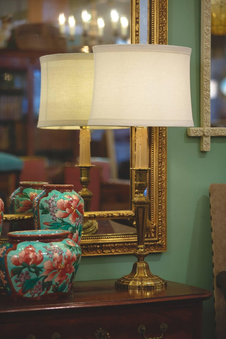 A beautiful candlestick table lamp made from polished and sculpted brass, French circa 1900. Lobed base with molded graduated levels, some textured and one gadrooned. Grooved, textured embellishments decorate the raised sections of the base. The