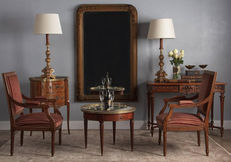 A highly decorated Napoleon III Period mantle mirror with its original gold leaf frame, French, circa 1870. Finely formed raised floral work adorns each corner, with roses and other flowers. Thick molding projects out all along the frame, with