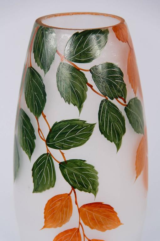 A tall, handblown frosted glass vase with hand-painted foliage motifs. This vase was found in the Loire region and dates from the early 1900s.
