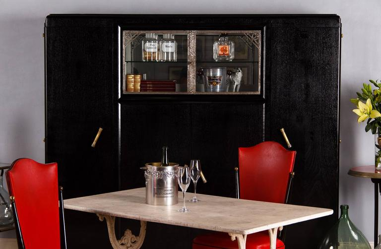 A stunning French Art Deco cabinet that was painted black with light grey interior. The piece was originally made in walnut veneer and is dated 1937 on the back of the mirror. The cabinet features four wooden doors with brass handles, paneled sides