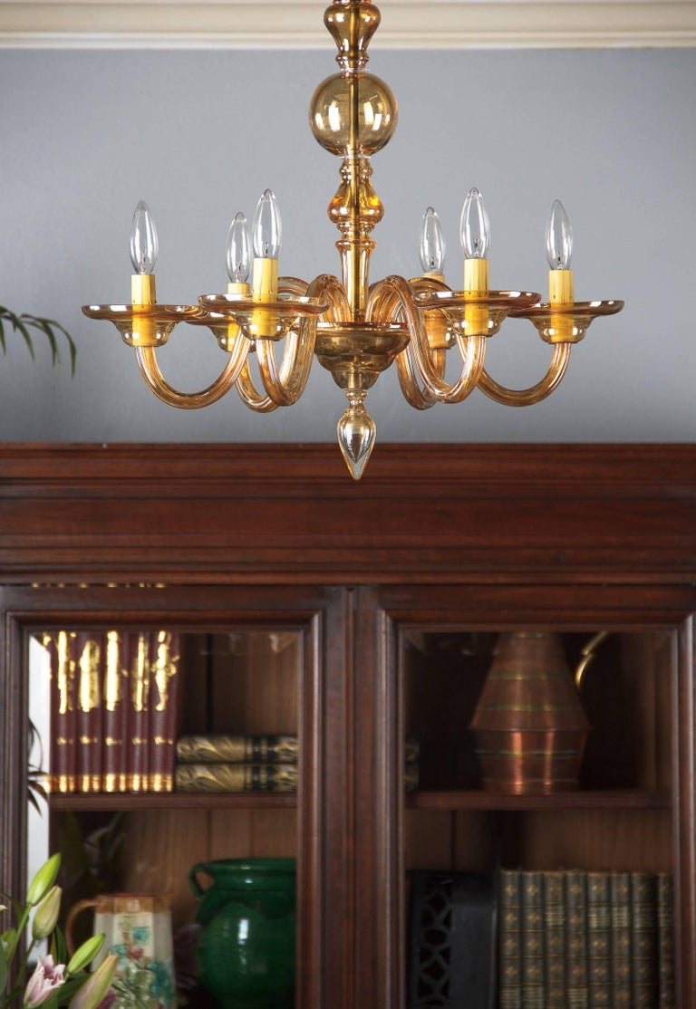 A classic elegant 1940s Italian Murano chandelier with six arms in amber glass with a shaped stem and canopy, ending with a finial. When you add the adjustable extension chain and canopy measuring 20