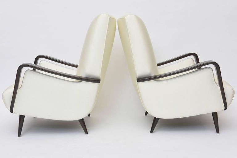 This pair of club chairs was designed by Melchiorre Bega in Italy during the 1950s. The pieces are made from dark walnut and features round tapered legs, splayed back feet and luxurious alabaster ivory colored upholstery.