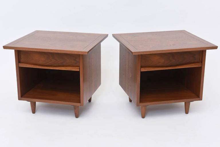 The square top with scored line border, above a drawer with highly figured walnut front and sculpted pull, above a cubby, on round tapering legs.