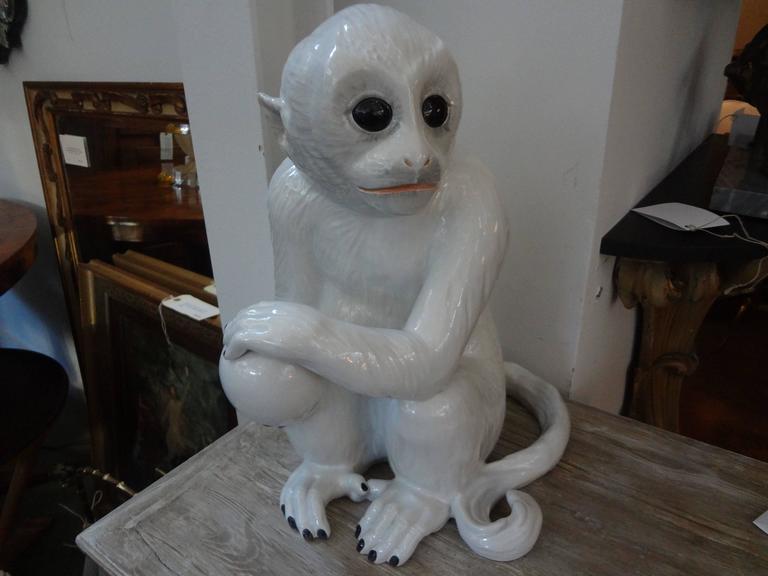 Italian midcentury Hollywood Regency white glazed pottery sculpture of a monkey, marked Italy, circa 1960.