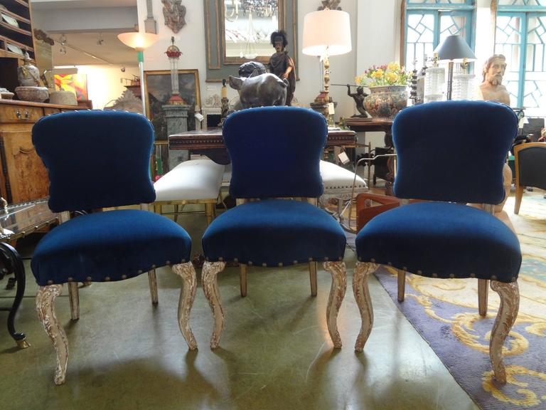 Stylish and comfortable set of six antique French Louis XV-XVI Style Maison Jansen attributed painted and gilt wood dining chairs with fabulous distressed patina. Taken down to frames and professionally reupholstered in dark blue velvet with spaced