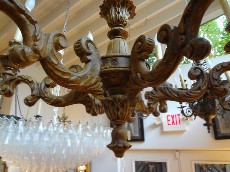 Italian Genovese six-arm patinated wood chandelier. This gorgeous hand carved Italian chandelier has been newly wired to U.S. specifications and dates to the 1920s.