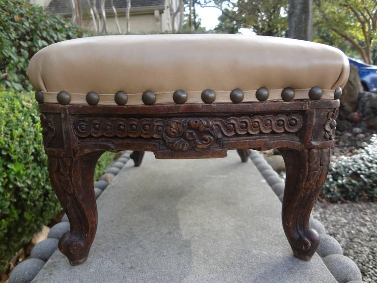 Well carved 19th century French Louis XV-XVI style foot stool or ottoman/tabouret. Newly upholstered in leather with spaced brass nailhead detail.
