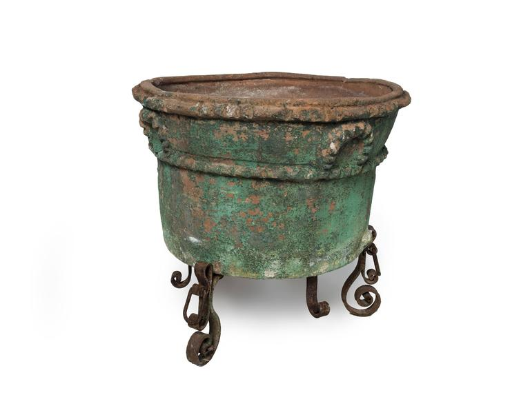Large painted terra cotta planter with a wrought iron stand.
