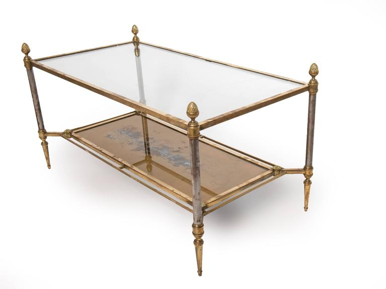 A rectangular brass-plated steel coffee table with a clear glass top and gold glass shelf below. The finials are solid brass. The posts are nickel plated which are showing some wear. The bottom gold glass shelf is worn from the underside which is