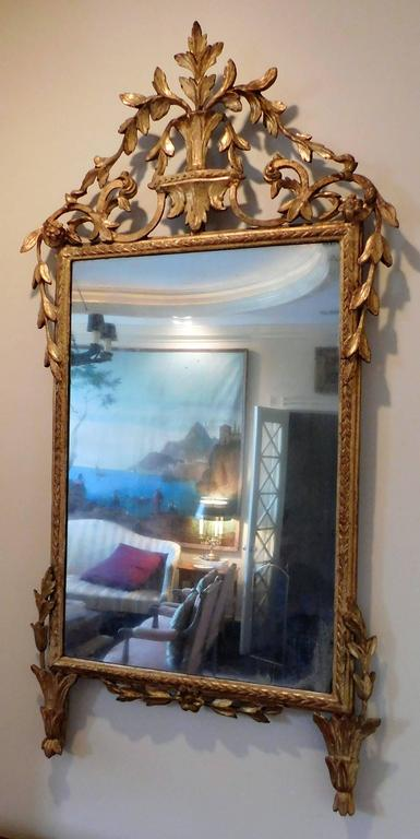 Probably made in Florence. Gilt and gold leaf on gesso on wood. Original wooden back. Mirror appears to be original. Excellent hand-carved foliate design.