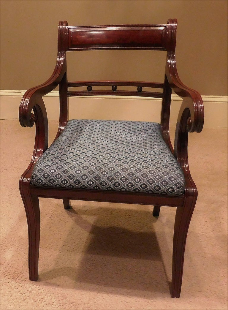 This set of 12 federal era chairs is comprised of two armchairs and ten side chairs. French polished mahogany frames have slip seats, eleven of which are covered in woven horse hair. Finely reeded with turned rosettes and figured mahogany veneered