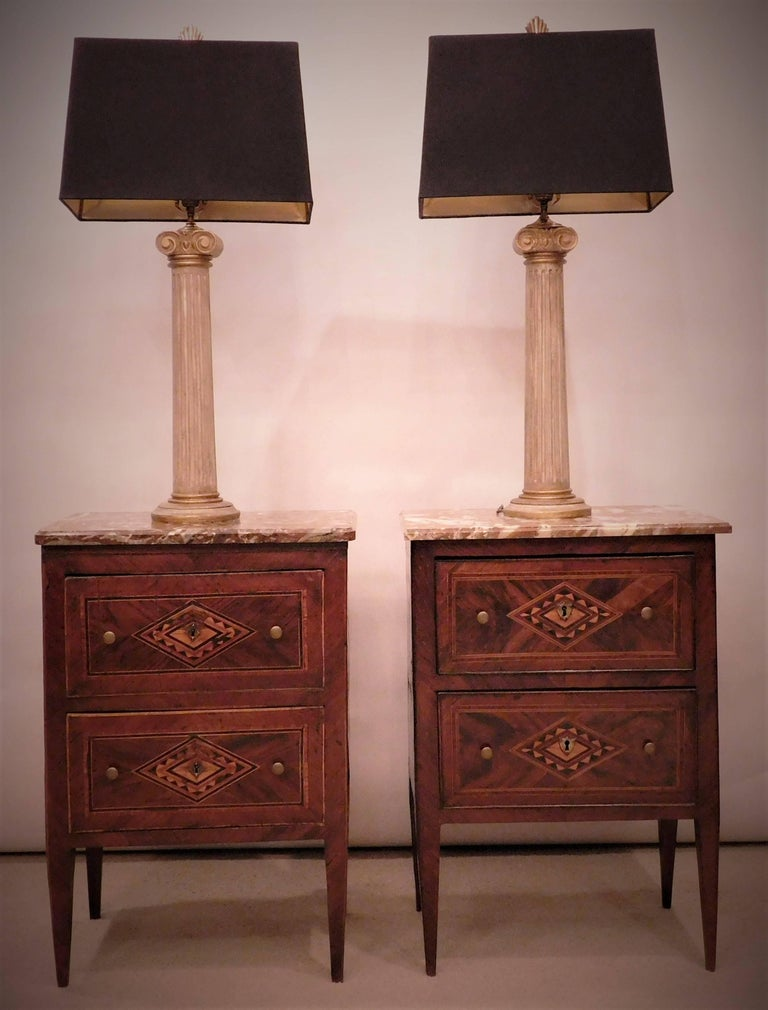 These two-drawer commodes appear to have been made in the same cabinet shop, but there are slight differences in the veneer designs. Also the marble tops, while similar in color, do not match.  As is often the case with pieces of this type, the