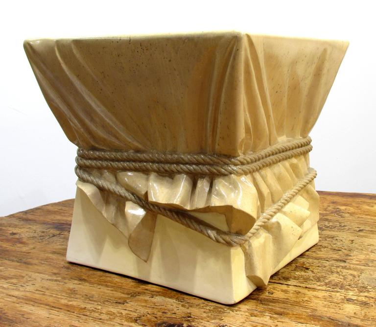 Surreal table or stool with the appearance of a draped form covered with fabric and tied with rope in the style of John Dickinson in original finish.